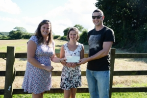 Newlyweds Laura and Nigel presenting £1,000 prize cheque to lucky guest Verity Lobb(centre)